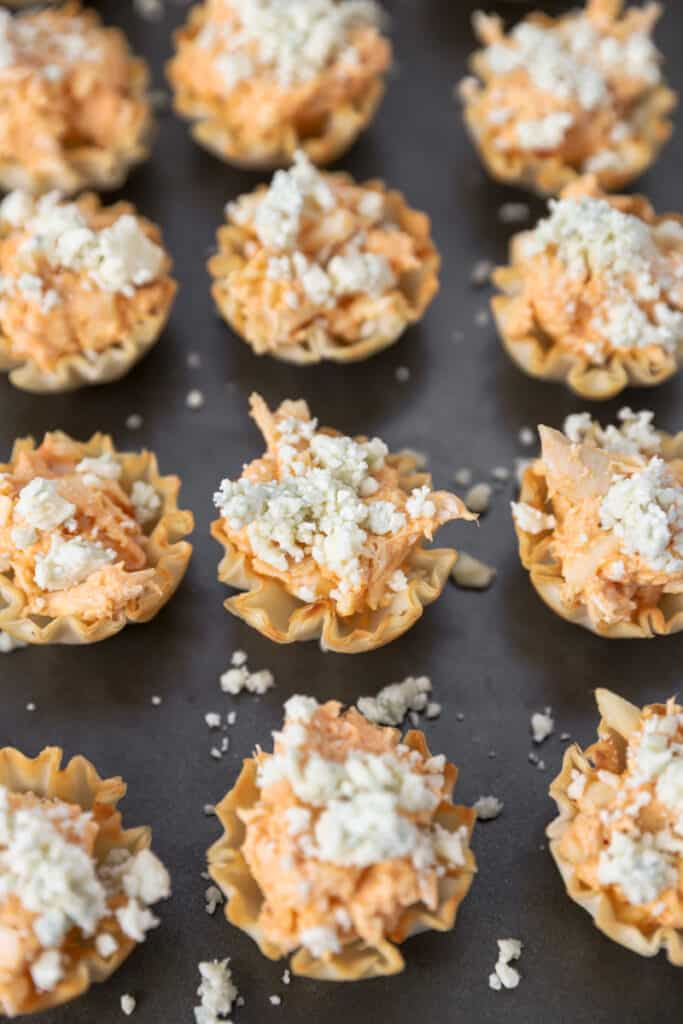 the filled phyllo cups now topped with blue cheese on a baking sheet.