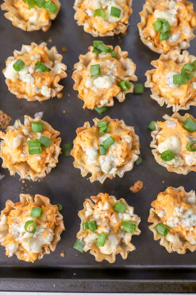 the baked buffalo chicken bites on a baking sheet topped with scallions