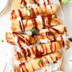 overhead shot of bbq chicken taquitos drizzled with ranch and bbq sauce on white newsprint paper.
