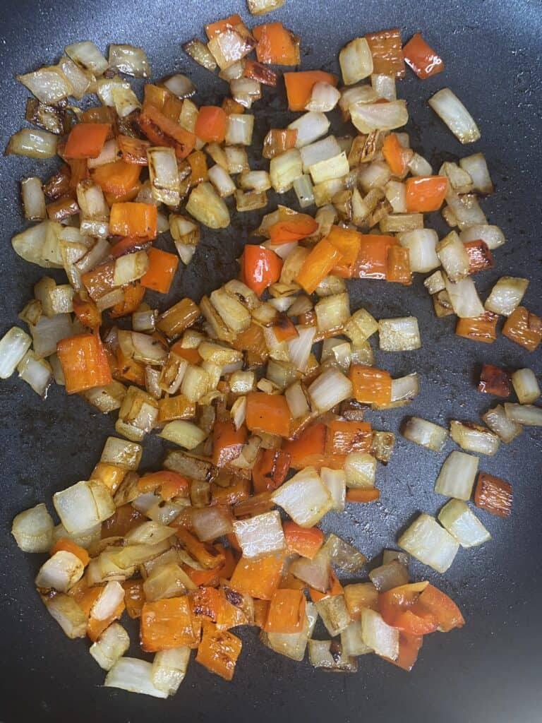 overhead shot of the white onions and red peppers in a pan.