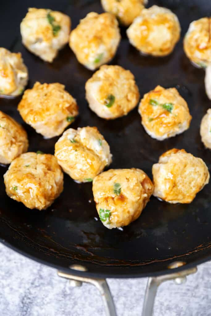 the chicken meatballs being browned in a black non-stick pan.