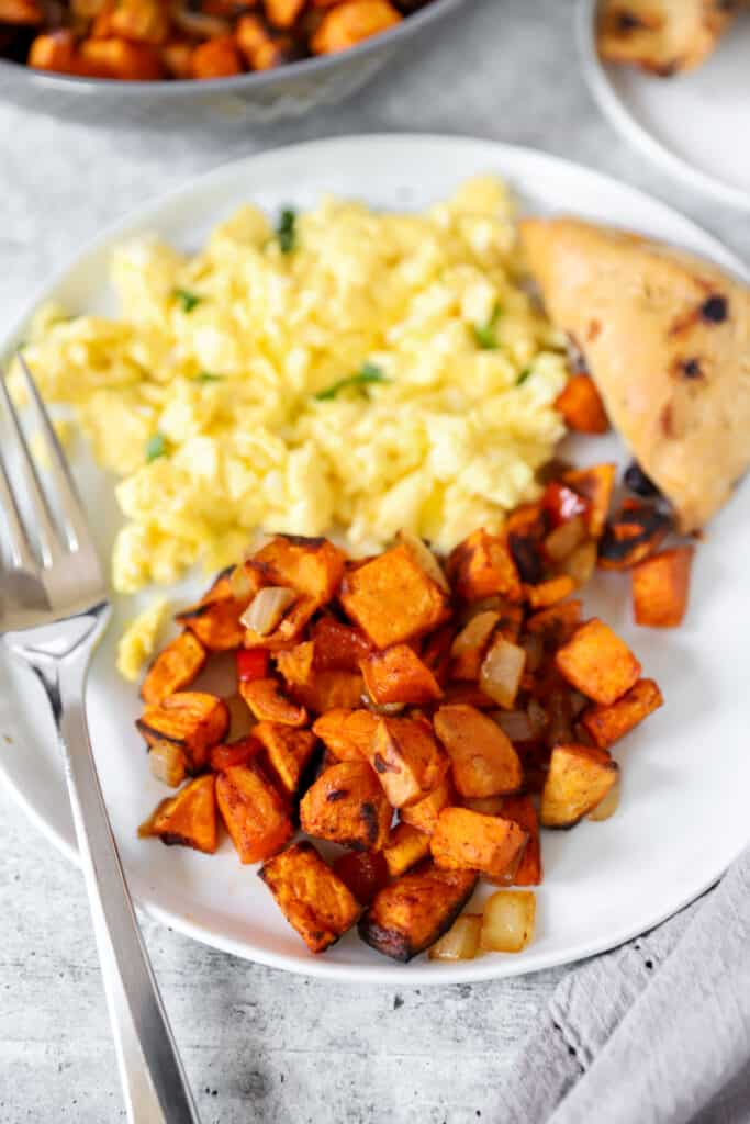 a plate with scrambled eggs, a blueberry scone, and the sweet potato home fries with a fork.