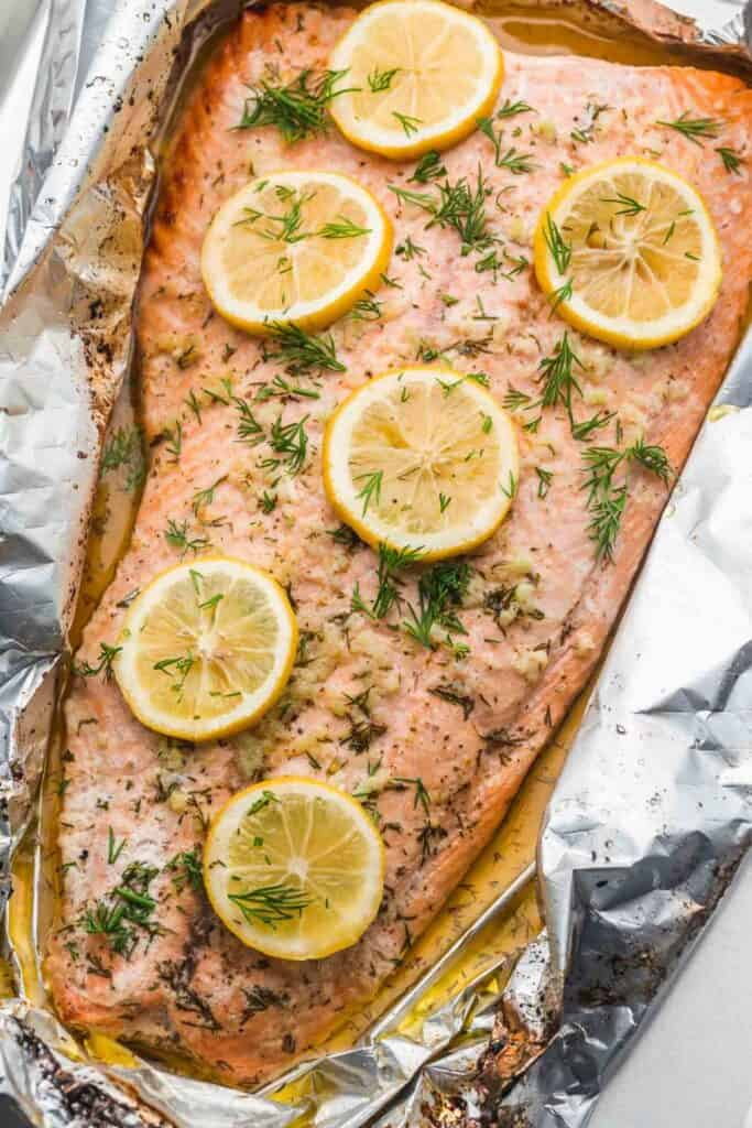 overhead shot of a large salmon filet covered in dill and lemon slices in foil.