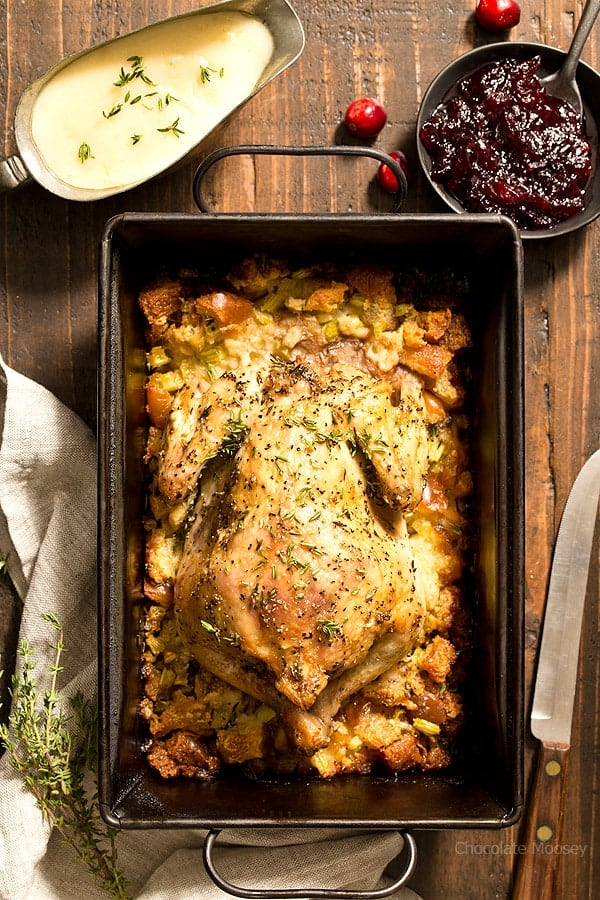 overhead shot of the cornish hen in a baking dish with stuffing on a wood surface.