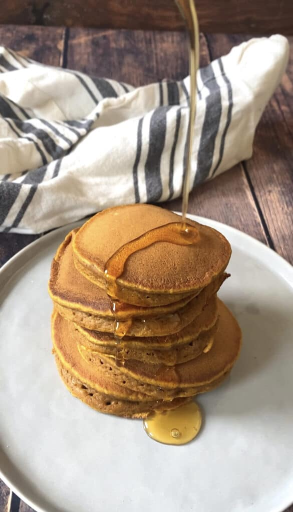 a stack of the pancakes on a wood surface with syrup being drizzle on.